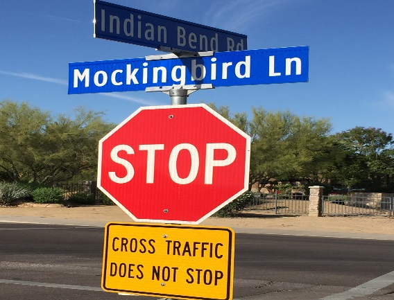 Indian Bend Road crossing Mockingbird Lane signs over Stop sign
